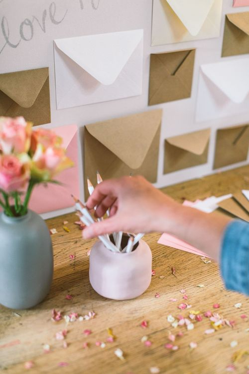 Person putting white pencils into a dusky pink pot next to a grey vase filled with pale pink antique roses as part of a DIY wedding card table set up