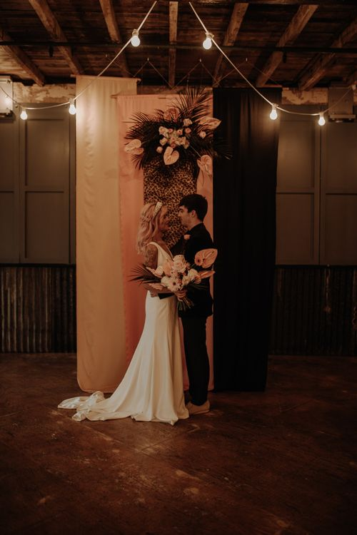 Bride and groom standing in front of fabric backdrop