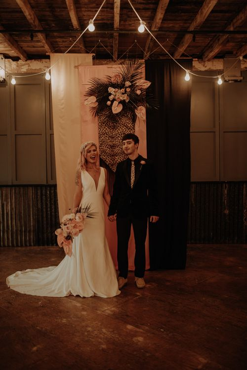 Stylish bride and groom standing in from tof blush and leopard print drapes