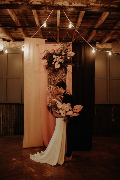 Bride and groom kissing in front of leopard print fabric backdrop