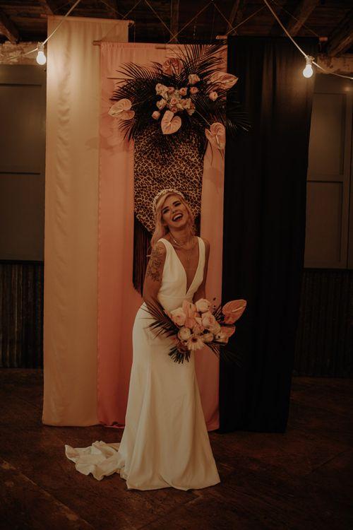 Stylish bride in minimalist wedding dress holding a tropical bouquet