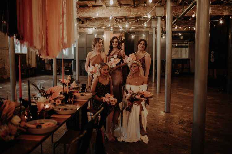 Bridal party in leopard print bridesmaid dresses sitting at the reception table