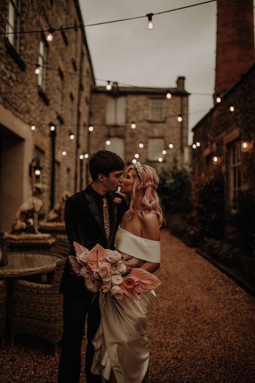 Stylish bride in off the shoulder dress under festoon lights