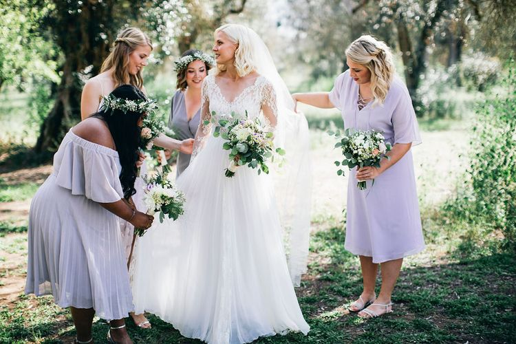 Bride in Long Sleeved Anna Kara Wedding Dress with Lace Bodice and Soft Skirt | Britten Weddings Floor Length Veil | Bridesmaids in Mismatched Lilac Dresses | Bouquets of White, Soft Pink, Purple and Yellow Flowers with Greenery | Flower Crowns | Puglian Countryside Wedding with Fairy Light Altar and Olive Grove Aperitivo | Figtree Wedding Photography