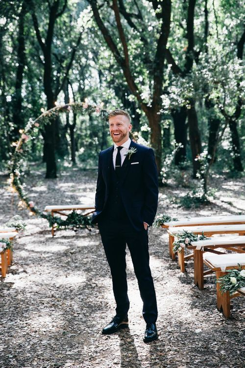 Groom in Dark Navy Hugo Boss Suit with Waistcoat and Black Patent Shoes by Common Projects | Fairy Light Moon Gate Altar | Festoon Lights | Puglian Countryside Wedding with Fairy Light Altar and Olive Grove Aperitivo | Figtree Wedding Photography