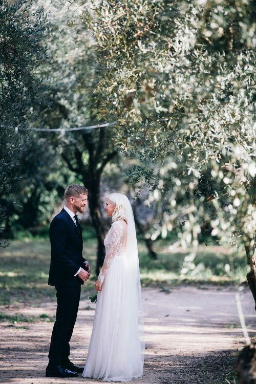 Just Married | Bride in Long Sleeved Anna Kara Wedding Dress with Lace Bodice and Soft Skirt | Britten Weddings Floor Length Veil | Groom in Dark Navy Hugo Boss Suit with Waistcoat and Black Patent Shoes by Common Projects | Puglian Countryside Wedding with Fairy Light Altar and Olive Grove Aperitivo | Figtree Wedding Photography