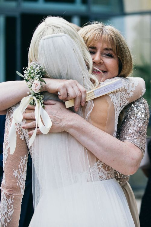 Hug from Mum | Bride in Long Sleeved Anna Kara Wedding Dress with Lace Bodice and Soft Skirt | Britten Weddings Floor Length Veil | Mother of the Bride in Taupe Adrianna Papell Dress with Sparkly Bodice and Soft Skirt | Puglian Countryside Wedding with Fairy Light Altar and Olive Grove Aperitivo | Figtree Wedding Photography