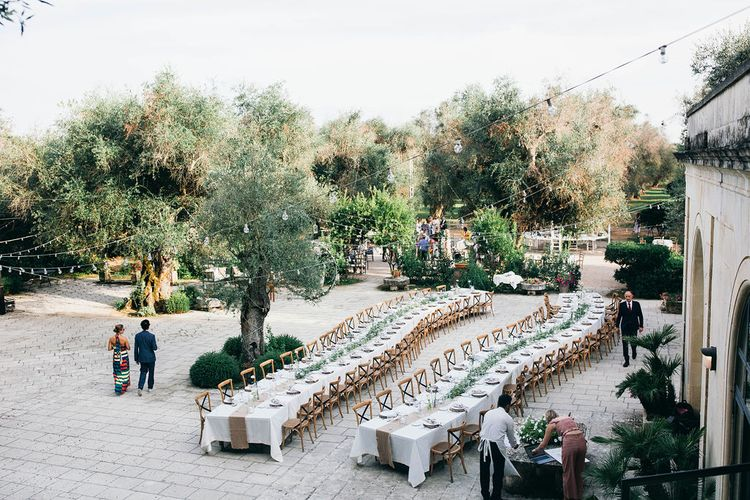 Outdoor Wedding Reception Decor at Tenuta Tresca | Long Tables Snaking Through Courtyard | Foliage Table Runners | Festoon Lights | Puglian Countryside Wedding with Fairy Light Altar and Olive Grove Aperitivo | Figtree Wedding Photography
