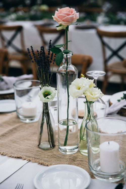 Outdoor Wedding Reception Decor at Tenuta Tresca | Hessian Table Runner | Mismatched Bud Vases | Glass Vases and Small Pillar Candles | Puglian Countryside Wedding with Fairy Light Altar and Olive Grove Aperitivo | Figtree Wedding Photography