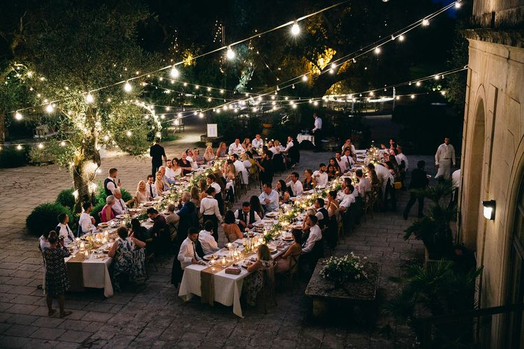 Outdoor Wedding Breakfast at Tenuta Tresca | Long Tables Snaking Through Courtyard | Foliage Table Runners | Festoon Lights | Tall Stemmed Candle Holders | Fairy Light Moon Gate | Puglian Countryside Wedding with Fairy Light Altar and Olive Grove Aperitivo | Figtree Wedding Photography