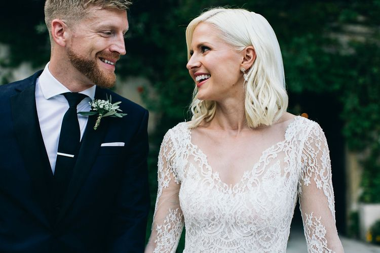 Bride in Long Sleeved Anna Kara Wedding Dress with Lace Bodice and Soft Skirt | Groom in Dark Navy Hugo Boss Suit with Waistcoat and Black Patent Shoes by Common Projects | Puglian Countryside Wedding with Fairy Light Altar and Olive Grove Aperitivo | Figtree Wedding Photography