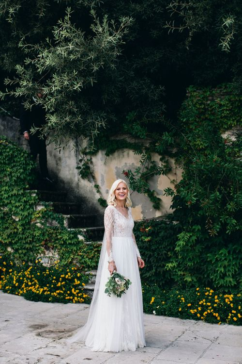 Bride in Long Sleeved Anna Kara Wedding Dress with Lace Bodice and Soft Skirt | Britten Weddings Floor Length Veil | Bridal Bouquet of White, Soft Pink, Purple and Yellow Flowers with Greenery | Puglian Countryside Wedding with Fairy Light Altar and Olive Grove Aperitivo | Figtree Wedding Photography