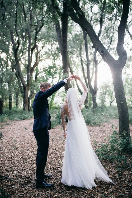 Bride in Long Sleeved Anna Kara Wedding Dress with Lace Bodice and Soft Skirt | Britten Weddings Floor Length Veil | Groom in Dark Navy Hugo Boss Suit with Waistcoat and Black Patent Shoes by Common Projects | Puglian Countryside Wedding with Fairy Light Altar and Olive Grove Aperitivo | Figtree Wedding Photography
