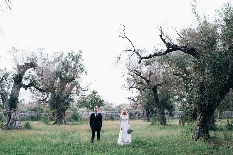 Bride in Long Sleeved Anna Kara Wedding Dress with Lace Bodice and Soft Skirt | Britten Weddings Floor Length Veil | Bridal Bouquet of White, Soft Pink, Purple and Yellow Flowers with Greenery | Groom in Dark Navy Hugo Boss Suit with Waistcoat and Black Patent Shoes by Common Projects | Puglian Countryside Wedding with Fairy Light Altar and Olive Grove Aperitivo | Figtree Wedding Photography