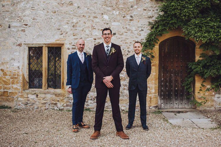 Groom in burgundy wedding suit with groomsmen