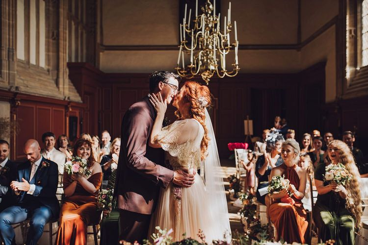 Bride and groom kiss at ceremony at Forde Abbey