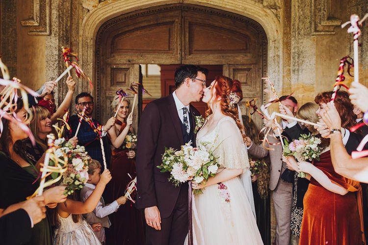 Guests wave ribbon at bride and groom
