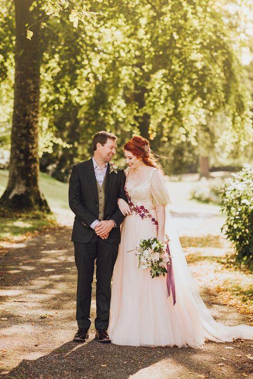 Bride in blush wedding dress with groom in burgundy wedding suit