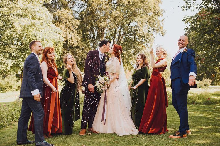 Bridal party throwing confetti over couple