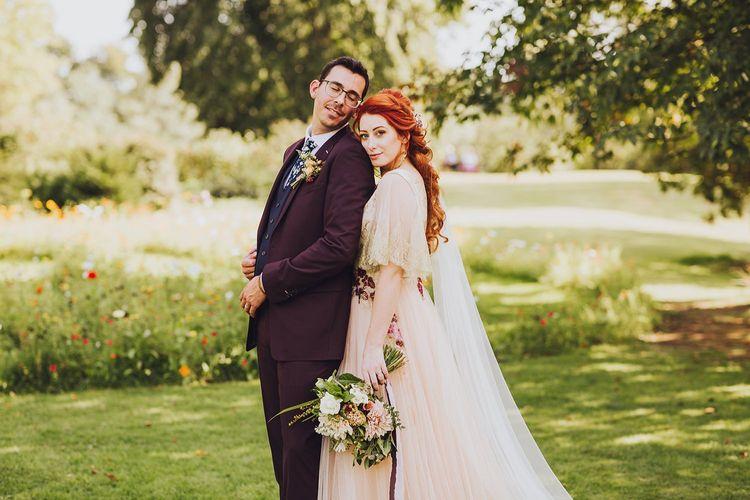 Burgundy wedding suit for groom with bride in bespoke wedding dress