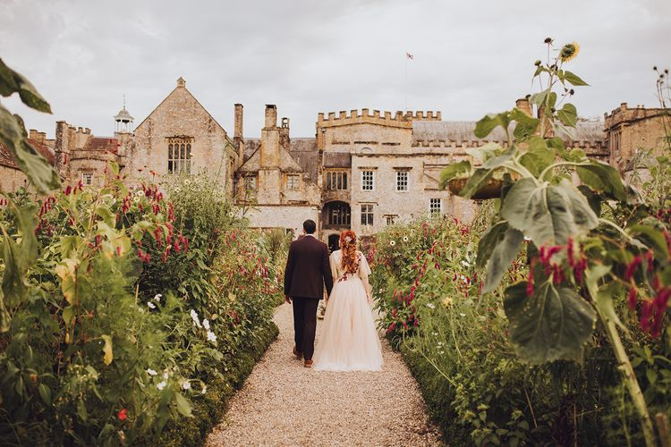 Bride and groom walk through the grounds of Forde Abbey