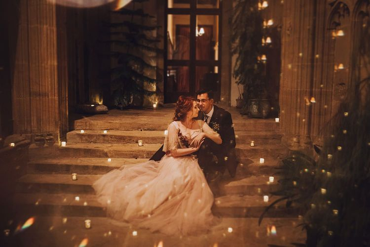 Bride and groom take a moment amongst candles