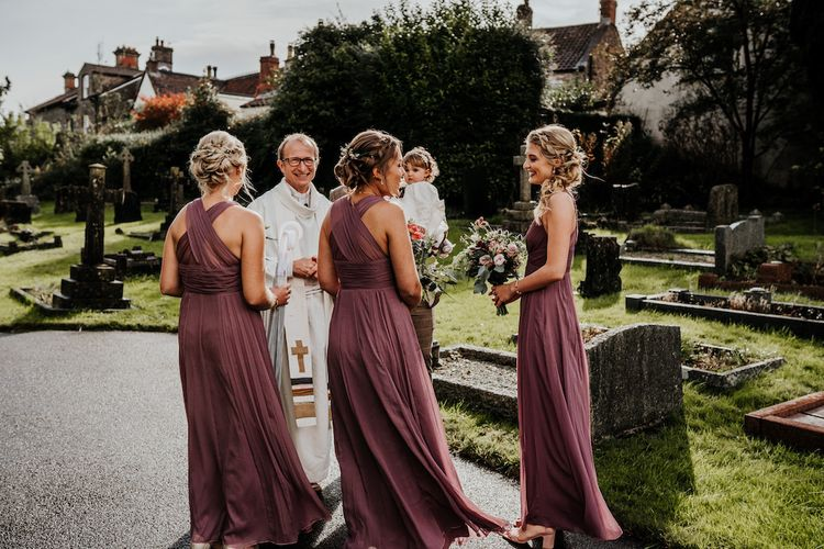 Bridal party outside the church in dusky pink dresses