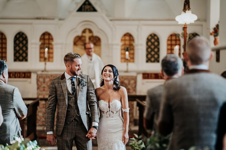 Bride in lace wedding dress and groom in brown check suit at church wedding ceremony
