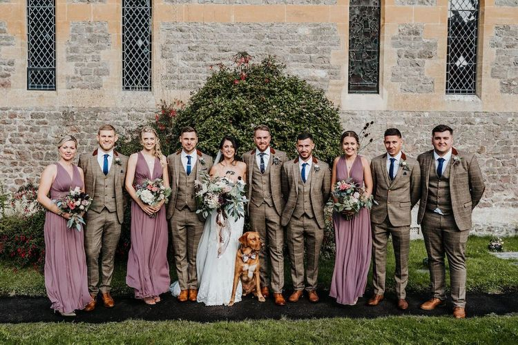 Wedding party portrait with bridesmaids in dusky pink dresses and groomsmen in beige check suits