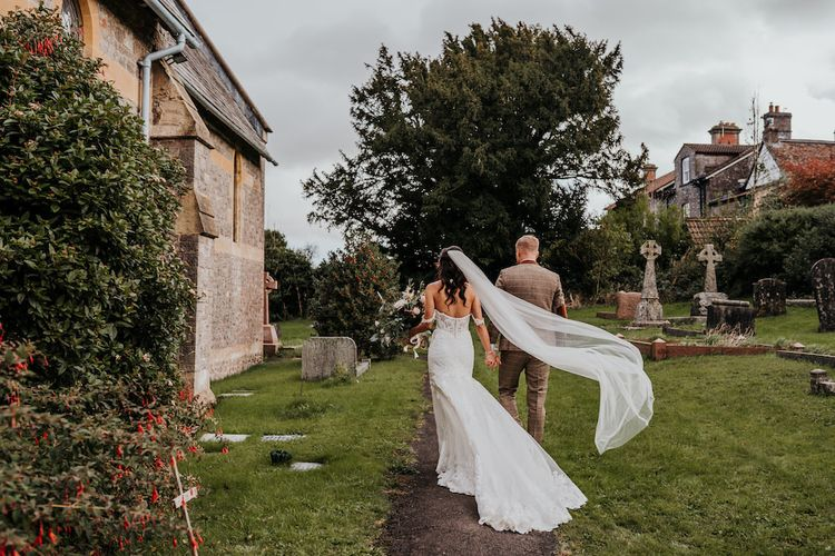 Bride in lace Martina Liana wedding dress with billowing veil walking through the church courtyard
