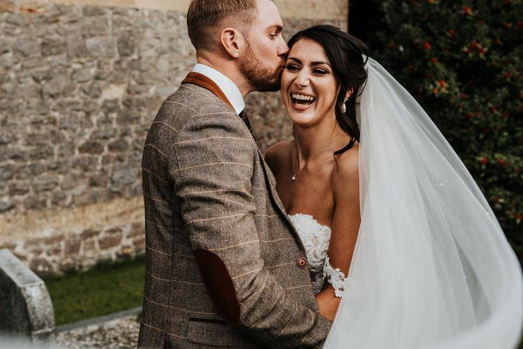 Groom in brown checked suit with elbow patches kissing his brides head