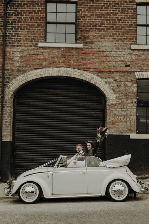 Bride and Groom Travelling in VW Beetle Wedding Car