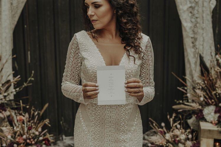 Bride in Boho Lace Wedding Dress Holding Menu Card