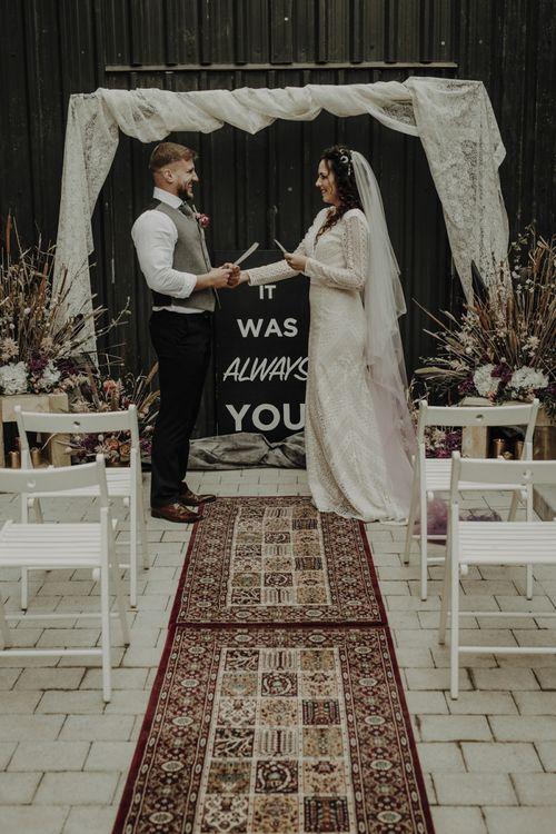Boho Bride and Groom Standing at the Altar with Woven Rug, Bold Sign and Dried Flower Arrangements