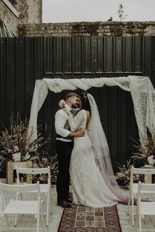 Boho Bride in Lace Wedding Dress and Groom Kissing at the Altar with Drapes, Woven Rug, Bold Sign and Dried Flower Arrangements