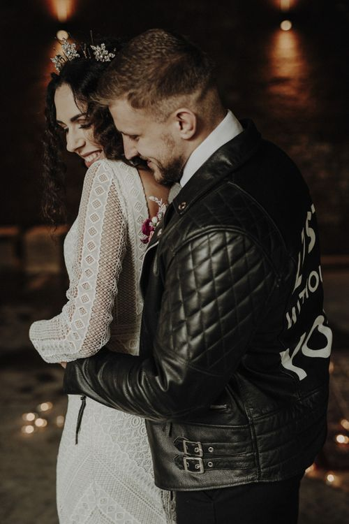 Groom in Personalised Leather Jacket Embracing Bride in Lace Wedding Dress