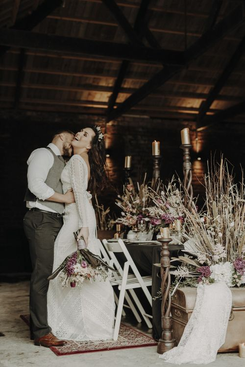 Boho Bride and Groom Standing Next to Tablescape and Dried Flower Arrangements