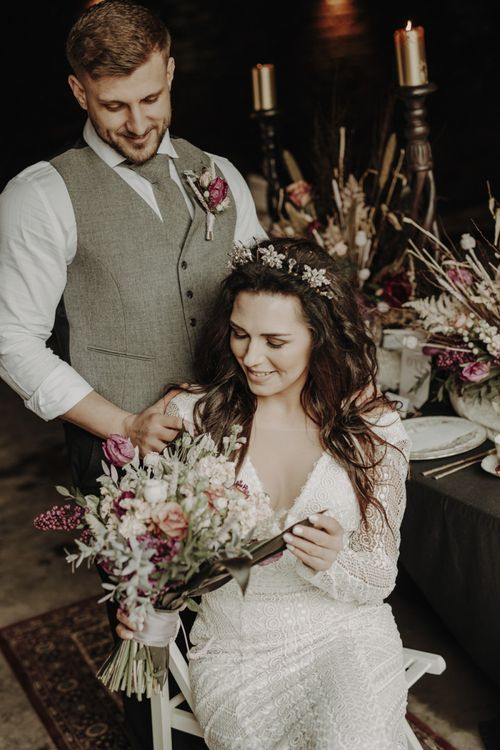 Boho Bride in Lace Wedding Dress Looking at White and Purple Wedding Bouquet
