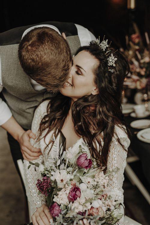 Groom in Wool Waistcoat Kissing Bride in Lace Wedding Dress
