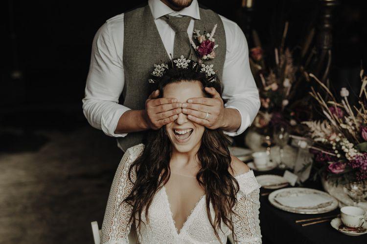Groom in Wool Waistcoat covering Brides Eyes  in Lace Wedding Dress and Crown Headpiece