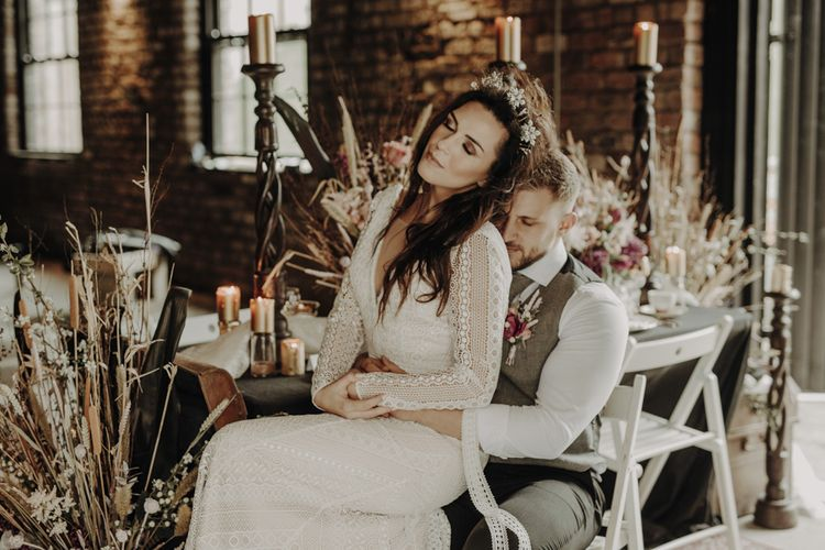 Boho Bride in Lace Wedding Dress and Groom in Wool Waistcoat Sitting at Rustic Tablescape with Dried Flower Decor and Floral Tableware