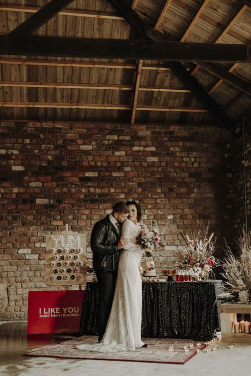 Boho Bride in Lace Wedding Dress and Groom in Leather Jacket Standing at Dessert Table