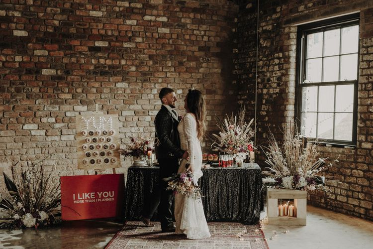 Boho Bride in Lace Wedding Dress and Groom in Leather Jacket Standing at Dessert Table with Doughnut Wall, Wedding Cakes and Dried Flower Arrangements