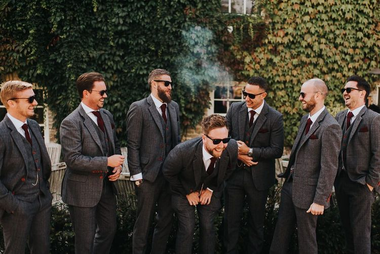 Groom and groomsmen in grey suits at wedding with light box sign and airstream photo booth