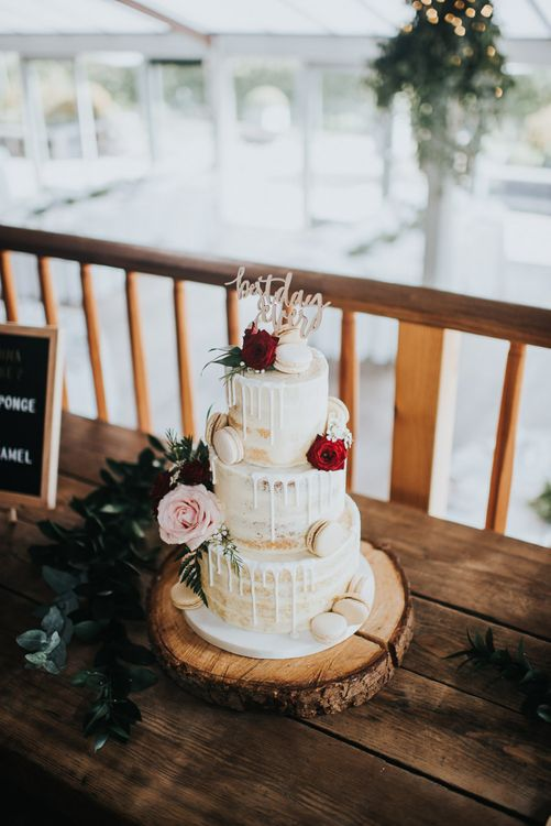 Semi-naked drip wedding cake at celebration with light box sign and pegboards