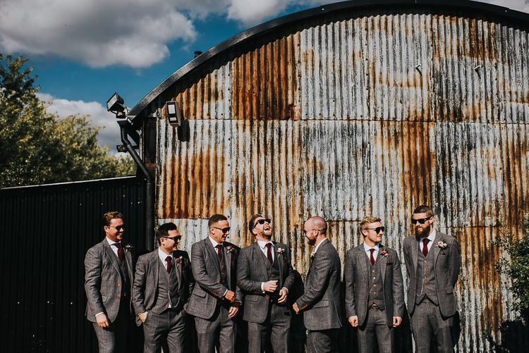 Groomsmen at Stone Barn wedding venue with light box sign and airstream photo booth