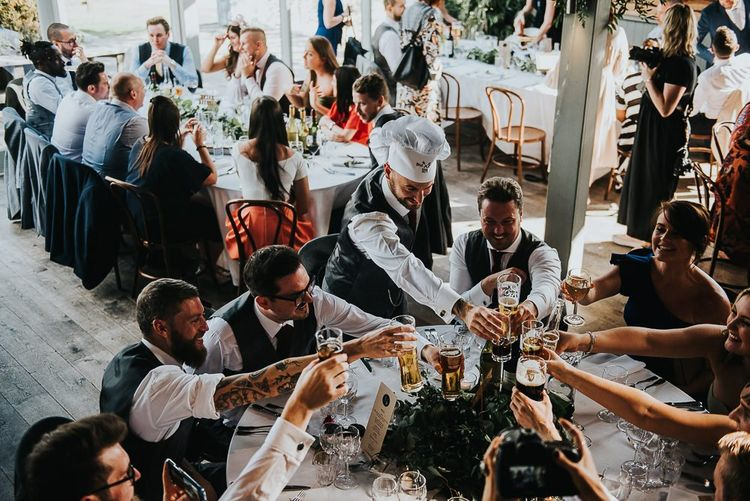 Wedding guests cheers during dinner in Stone Barn