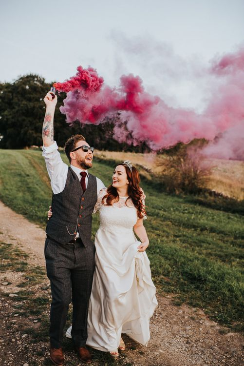 Bride and groom at wedding with smoke flares and light box sign