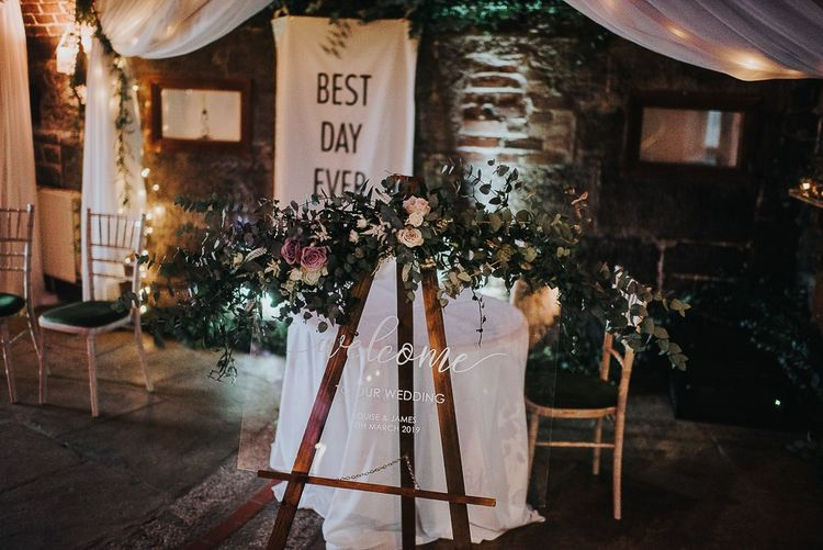 Acrylic Wedding Sign Resting on an Easel with Floral Garland