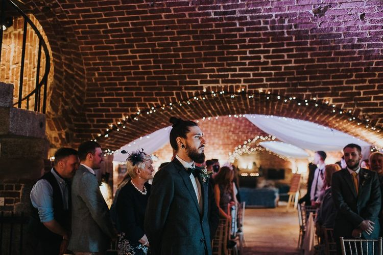 Groom in Bow Tie and Top Knot Standing at the Altar